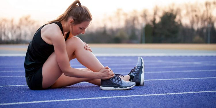 Athlete woman has ankle injury, sprained leg during running training
