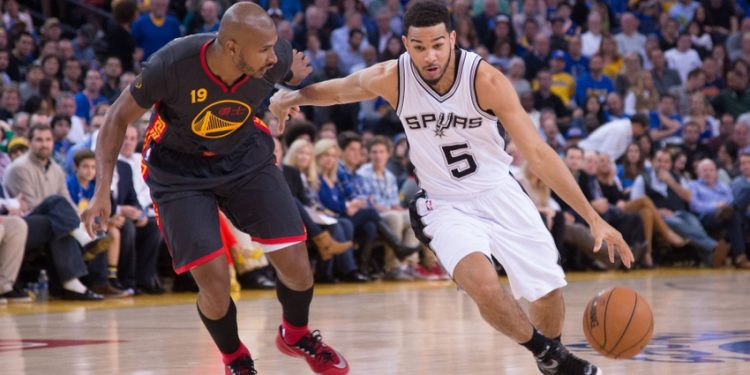 February 20, 2015; Oakland, CA, USA; San Antonio Spurs guard Cory Joseph (5) dribbles the basketball against Golden State Warriors guard Leandro Barbosa (19) during the third quarter at Oracle Arena. The Warriors defeated the Spurs 110-99. Mandatory Credit: Kyle Terada-USA TODAY Sports